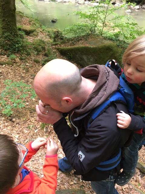 Mann und Kinder beim Grashalmpfeifen